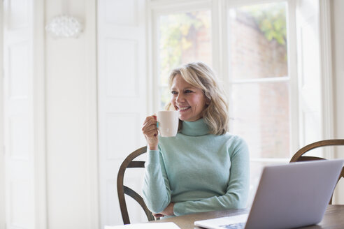 Smiling mature female freelancer drinking tea and working at laptop at home - HOXF03554