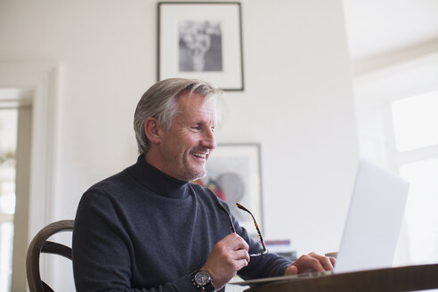 Smiling mature male freelancer working at laptop at home - HOXF03560