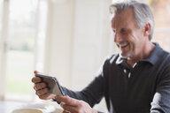 Smiling mature man using smart phone - HOXF03569
