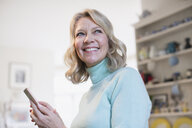 Portrait smiling, confident mature woman texting with smart phone - HOXF03596