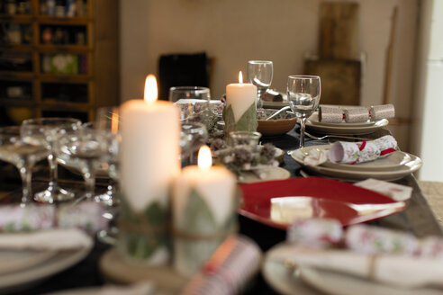 Candles, placesettings and Christmas crackers on table - CAIF20516