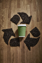 Coffee beans forming recycle symbol around green recyclable coffee cup - CAIF20540