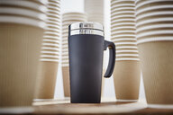 Insulated drink container surrounded by disposable coffee cups - CAIF20543