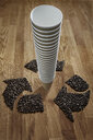 Coffee beans forming recycle symbol around stack of recyclable coffee cups - CAIF20546