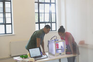 Designers watching 3D printer in office - CAIF20579