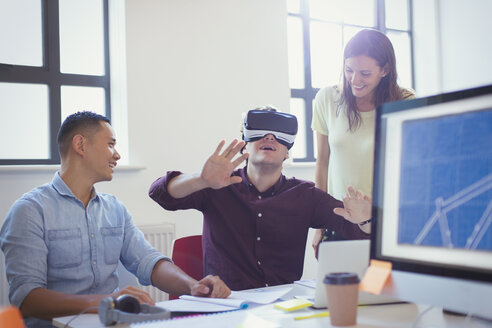 Computer programmers testing virtual reality simulator glasses in office - CAIF20597