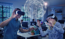 Computer programmers testing virtual reality simulator glasses, viewing futuristic hologram - CAIF20630