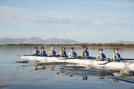Female rowing team rowing scull on sunny lake - CAIF20648