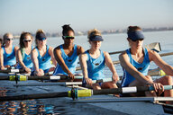 Female rowers rowing scull on sunny lake - CAIF20663