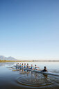 Female rowers rowing scull on tranquil lake under blue sky - CAIF20678