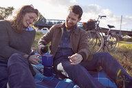 Couple enjoying coffee break on marshes - CUF09959