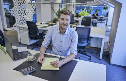 Portrait of smiling businessman sitting at desk in open-plan office - BEF00072