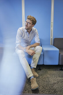 Portrait of businessman sitting on light blue stool in an office - BEF00078