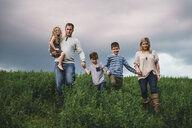 Family of five enjoying outdoors on green grassy field - CUF09998