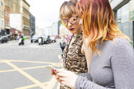 Two retro styled young women strolling along city street looking at smartphone - CUF10019