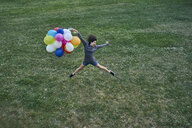 Happy young woman with bunch of balloons jumping in the air on a meadow - BEF00081