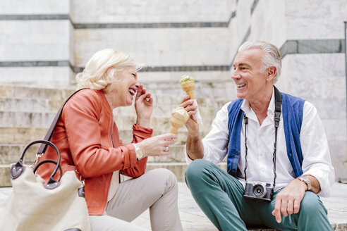 Tourist couple eating ice cream cones and laughing in Siena, Tuscany, Italy - CUF10428