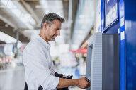 Mature man using ticket machine at train station - CUF10437