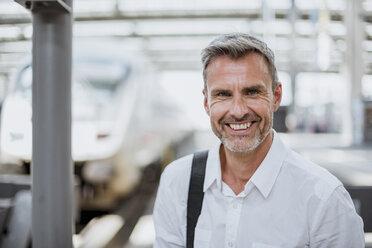 Portrait of mature man on station platform, smiling - CUF10443