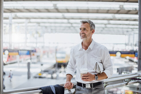 Mature man at train station, holding takeaway coffee cup - CUF10446