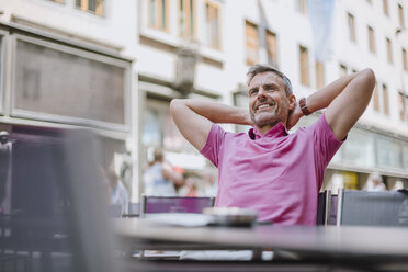 Mature man sitting outside cafe, hands behind neck, relaxing - CUF10452