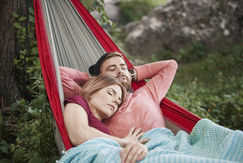 Couple relaxing in hammock, eyes closed sleeping, Krakow, Malopolskie, Poland, Europe - CUF10485