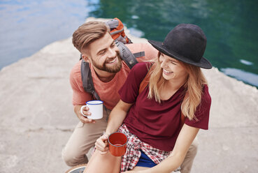 Couple by water holding enamel mugs smiling, Krakow, Malopolskie, Poland, Europe - CUF10518