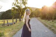 Woman on rural road wearing strapless dress looking over shoulder at camera smiling - CUF10524