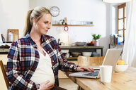 Pregnant woman holding stomach whilst looking at laptop on table - CUF10576