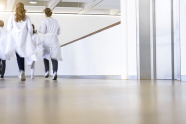 Rear view of male and female doctors running in hospital corridor - CUF10588