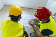 Two workers looking at construction plan - KIJF01933
