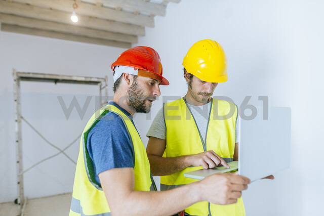 Workers using laptop at construction site - KIJF01936