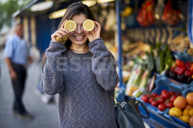 Laughing young woman on market covering her eyes with lemon halves - BEF00084