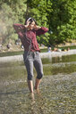 Young woman listening music with headphones and cell phone dancing at riverside - BEF00087