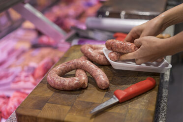 Female butcher cutting sausage - AFVF00452