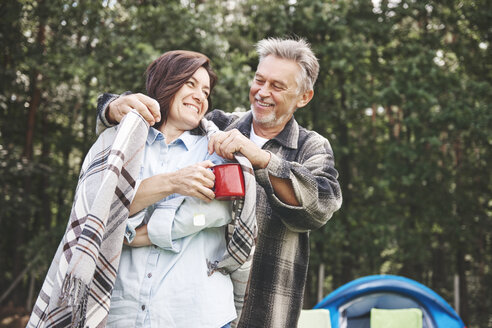 Mature couple standing beside tent, man putting blanket around woman's shoulders - CUF10645