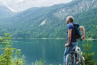 Senior man, leaning on bicycle, looking at view, Elbsee, Bavaria, Germany - CUF10660