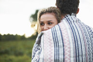 Young couple hugging wrapped in blanket in field - CUF10735