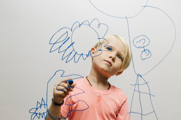 Boy admiring his marker pen drawing on glass wall - CUF10741
