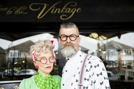Serious portrait of a quirky vintage couple outside vintage shop - CUF10777
