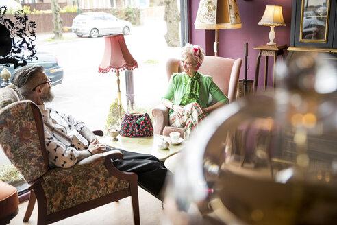 Happy quirky vintage couple having tea in tea rooms - CUF10786