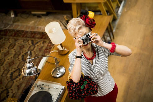 Quirky woman taking photographs on vintage camera in antiques emporium - CUF10792