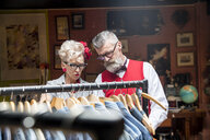 Quirky vintage couple shopping in vintage and antique emporium - CUF10795