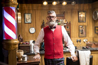 Portrait of quirky senior man in traditional old english barber shop - CUF10798