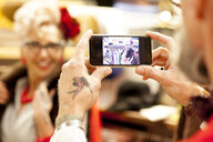 Tattooed hands of senior man taking smartphone photo of girlfriend in antique and vintage emporium - CUF10804