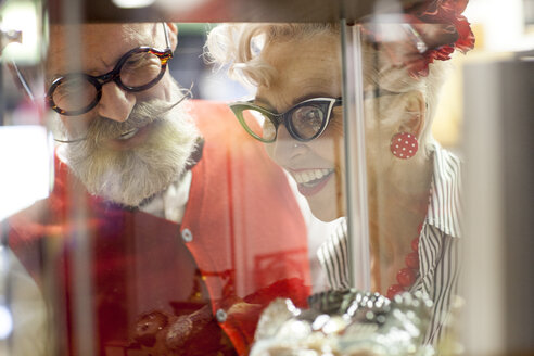 Quirky vintage couple looking at glass display case in antique emporium - CUF10807
