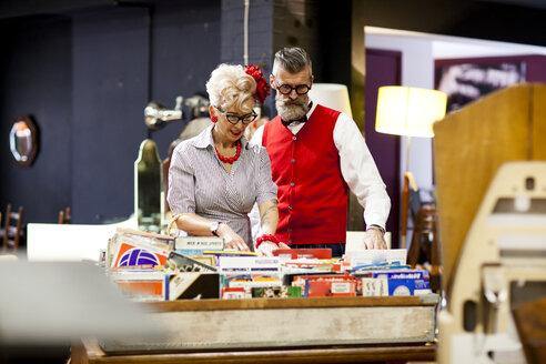 Quirky vintage couple looking at vinyl records in antique and vintage emporium - CUF10810