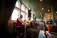 Quirky couple relaxing in bar and restaurant, Bournemouth, England - CUF10846