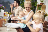 Couple with baby and toddler daughters at family lunch on patio table - CUF10861