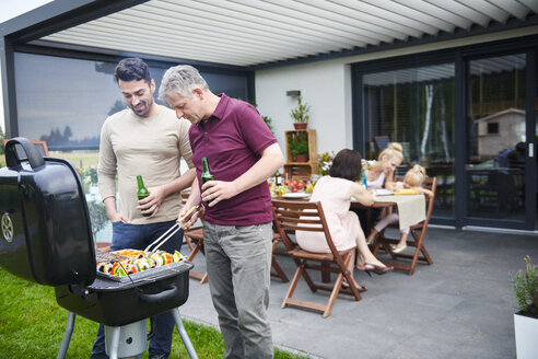 Mature and mid adult man barbecuing at family lunch on patio - CUF10864